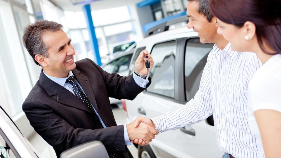 Couple buying a car and salesman handling keys