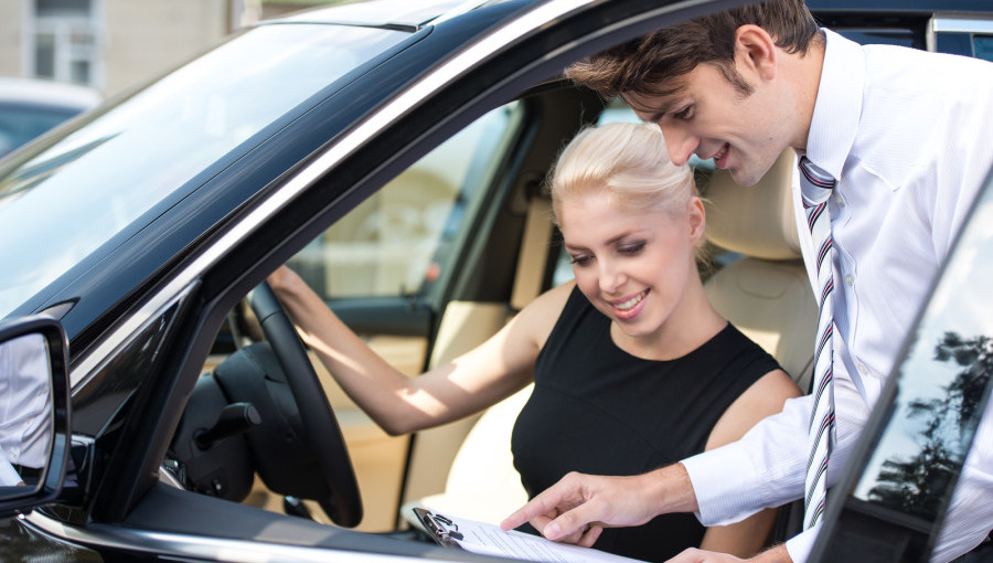 Car dealer and happy smiling woman signing a contract. Concept for car rental ** Note: Soft Focus at 100%, best at smaller sizes