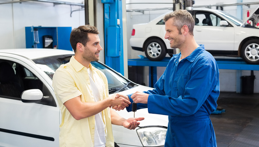 Customer shaking hands with mechanic giving keys at the repair garage