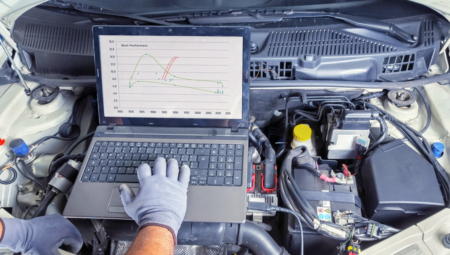 Professional car mechanic working in auto repair computer service