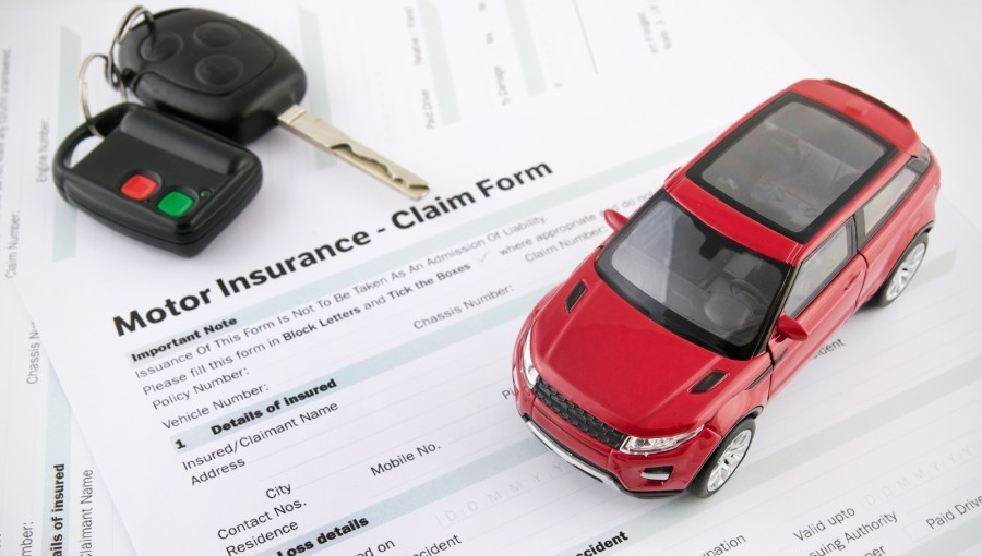 Car toy and keys on insurance documents . Protection car concept